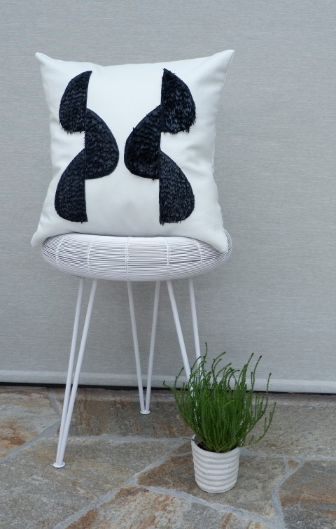White leather pillow with black fringes styled on white side table.