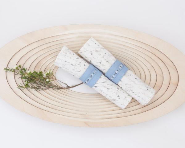 blue beaded leather napkin rings on wood platter
