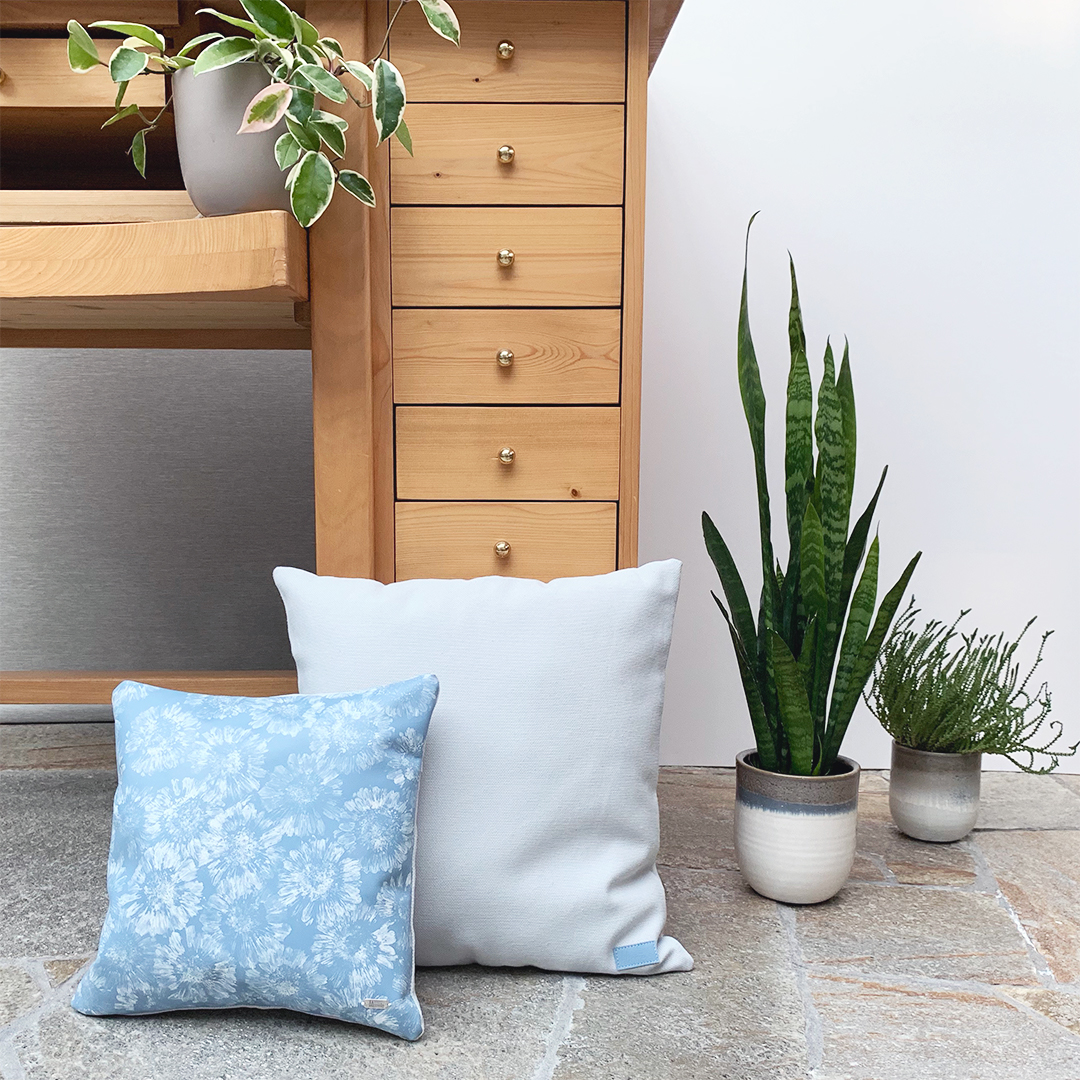 Blue leather Gerbera pillow styled with blue fabric pillow and flower pots with plants.