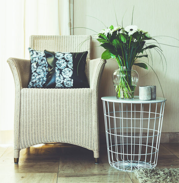 Black leather pillows in chair with side table and Gerbera flowers in vase.