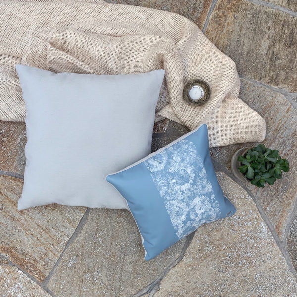 Blue leather 'IN BLOOM' pillow with Gerbera print styled with blue fabric pillow and plant.
