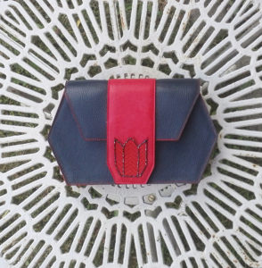 Handmade leather clutch in blue and red with pearls.