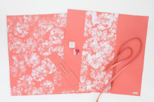 Gerbera print in white paint on coral colored leather.