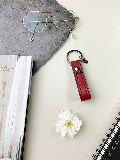 FLATLAY WINE RED LEATHER KEYCHAIN AND WHITE FLOWER