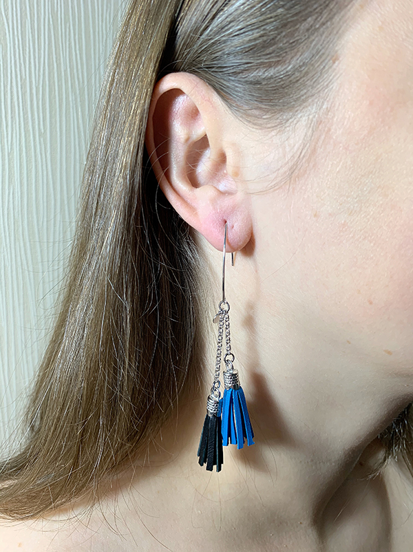 Sterling silver earrings with serenity and black leather tassels and round logo tag. Styled in ear