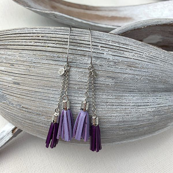 Sterling silver earrings with dark purple and lavender leather tassels and round logo tag