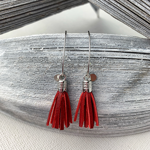 Sterling silver earrings with dark red leather tassels and round logo tag