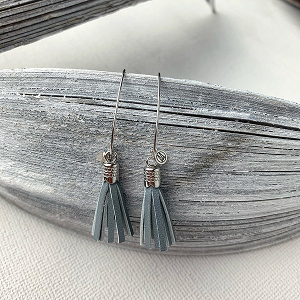 Sterling silver earrings with grey blue leather tassels and round logo tag