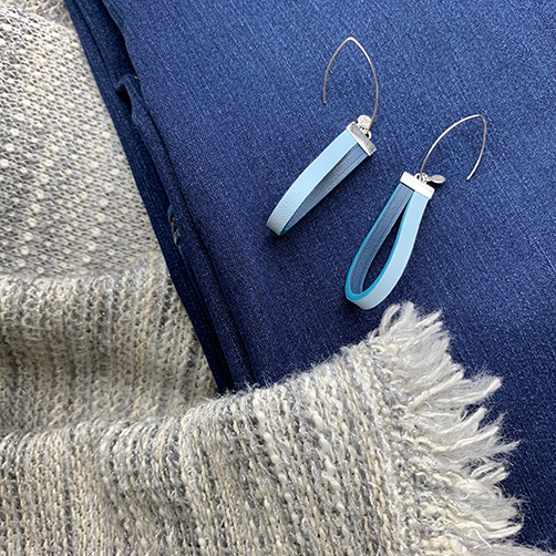 Sterling silver earrings with a baby blue and dark blue leather loop. Flatlay of leather earrings styled with a pair of blue jeans and a grey bouclet jacket.
