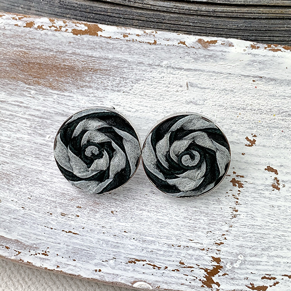 Sterling silver frame earrings with a black and white leather woven piece close up
