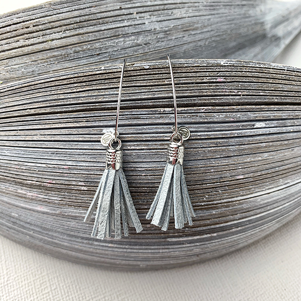 Sterling silver earrings with silver leather tassels and round logo tag