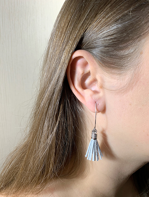 Sterling silver earrings with silver leather tassels and round logo tag. in ear look