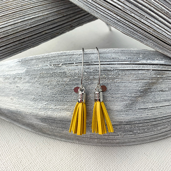 Sterling silver earrings with yellow leather tassels and round logo tag