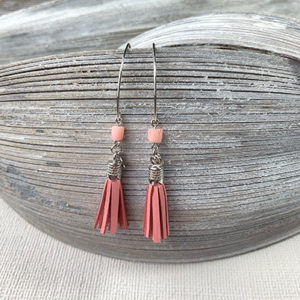Sterling silver earrings with pastel pink bamboo coral beads and pink leather tassels, and round logo tag