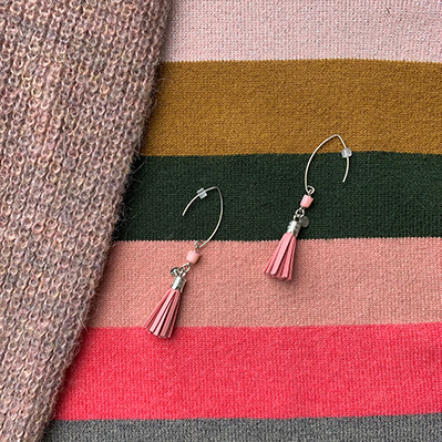 Sterling silver earrings with pastel pink bamboo coral beads and pink leather tassels, and round logo tag combined with a pastel pink knit and striped sweater