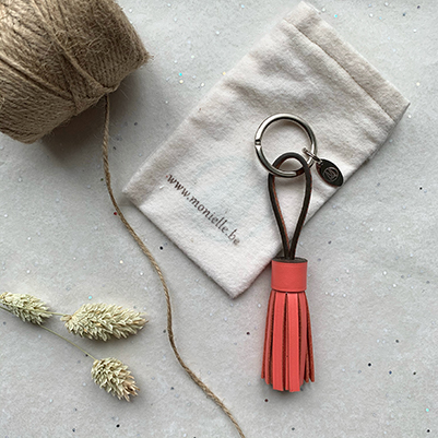 Flatlay tassel keychain in coral, ribbon, dried flowers and fabric packaging