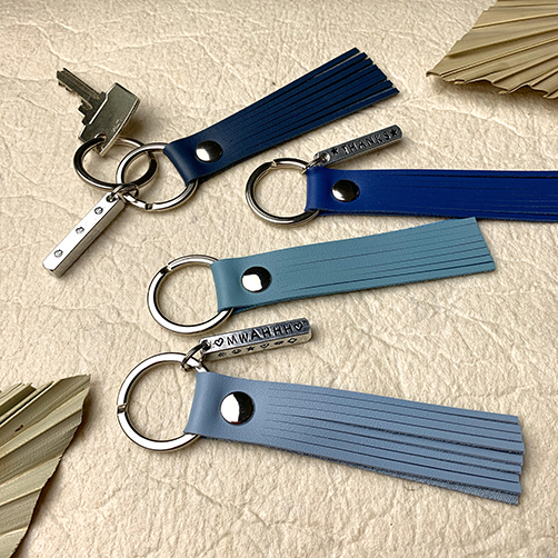 Flatlay of 4 leather tassel keychains in light blue, mint, royal blue and dark blue with personalized metal bars, and 2 dried leaves.