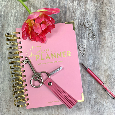 Flatlay with a pink power planner, hot pink leather tassel keychain wit personalized metal bar, pink pen and a bright pink tulip.