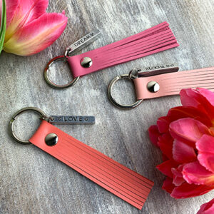 Flatlay of 3 leather tassel keychains in nude pink, hot pink and coral colour with personalized metal bars, and 2 pink tulips.
