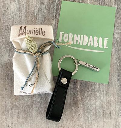 Stoffen cadeauzakje met blauwe koorden en logo , zwarte lederen sleutelhanger, en postkaart met het woord FORMIDABLE