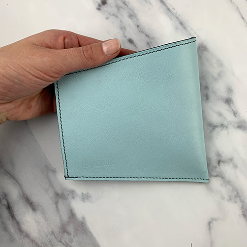 Hand holding leather face mask sleeve in sky blue leather with stitched decoration