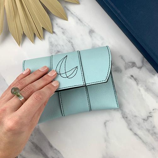 Lederen pochette in hemelsblauw met decoratief stiksel