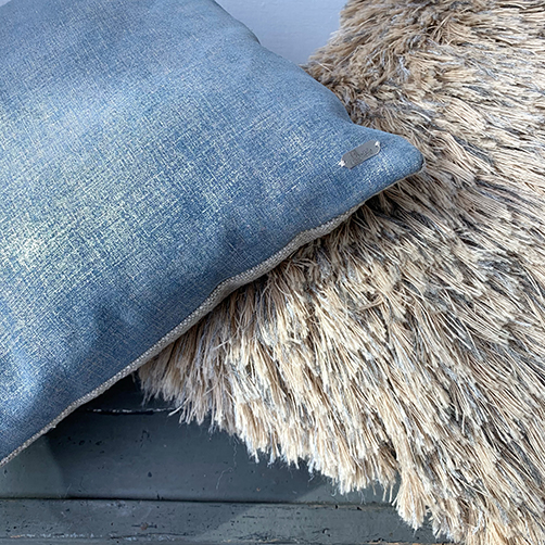 Close up of fabric long haired pillow and blue leather pillow