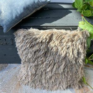 Sierkussen fluffy met lange haren in tinten van beige gecombineerd met een vintage grijze houten kist en groene plant