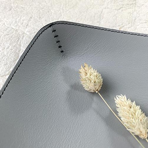 Detail handgenaaide steken in zwarte linnen draad